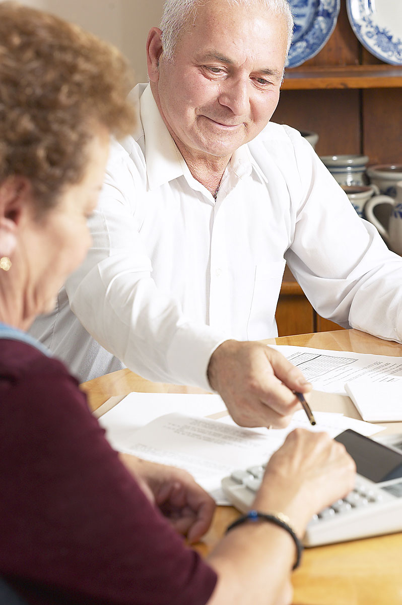 Two Older Adults Preparing Finances at a Table