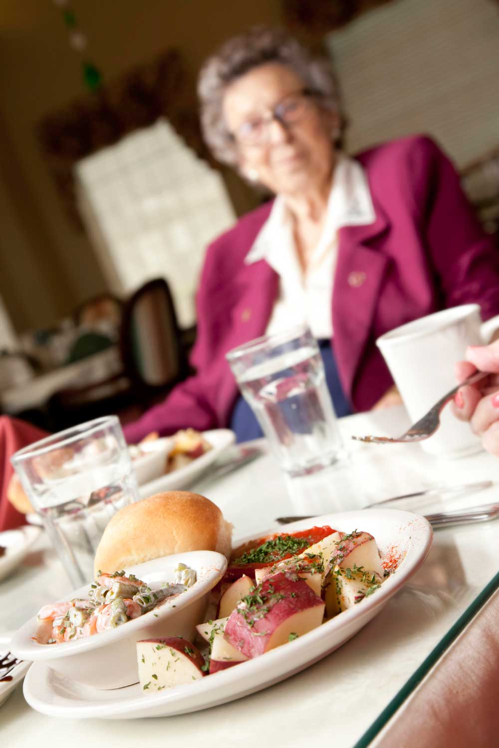 Older Woman Sitting at Table in Lunch Room